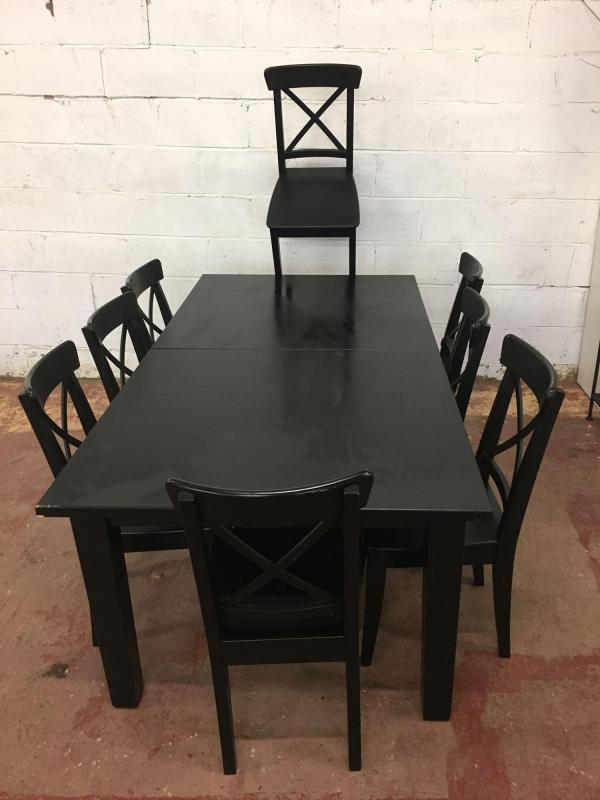 A Large Black Wooden Ikea Extendable Dinning Table And A Set Of 8